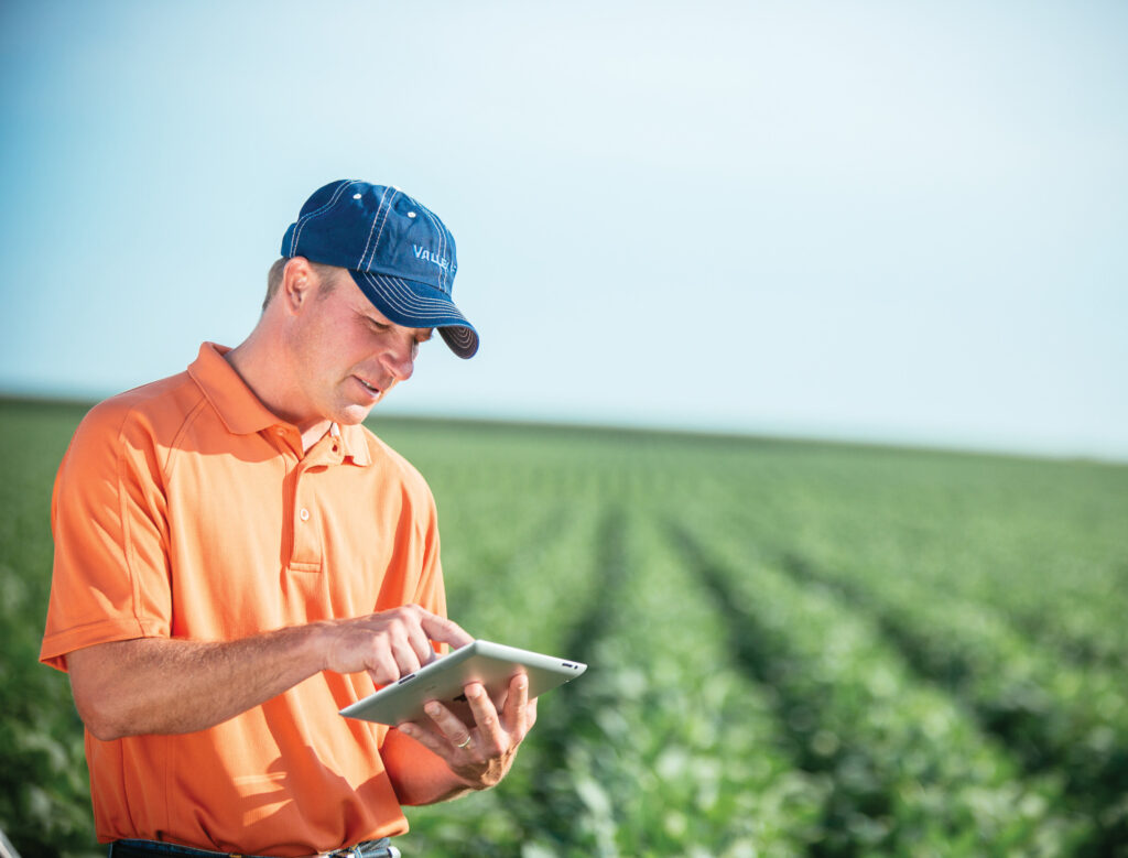 Man looking at iPad using Autonomous Crop Management Technology